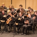 Members of the Appalachian Guitar Orchestra play onstage.