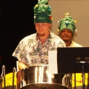 Two members of the Steely Pan Steel Band play steel drums while wearing Christmas tree hats.