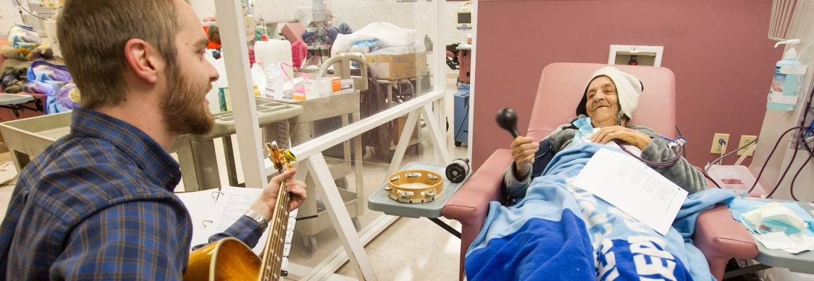Hayes School of Music music therapy student playing guitar for patient